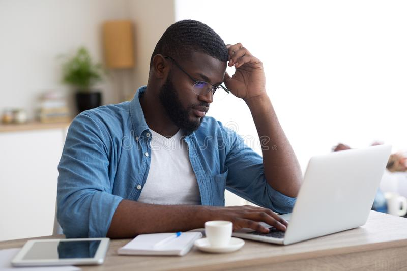 Frustrated african man working on laptop computer, having problems at work stock photography