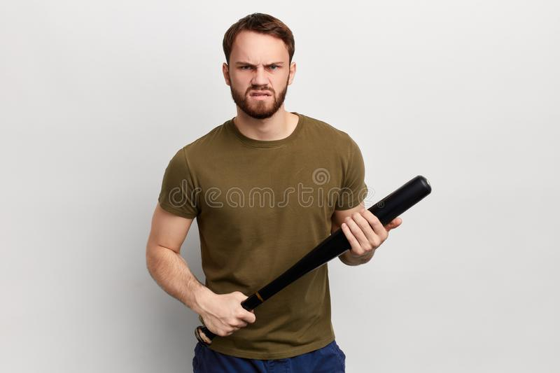 Frustrated angry guy holding a bat, looking at the camera, royalty free stock photography