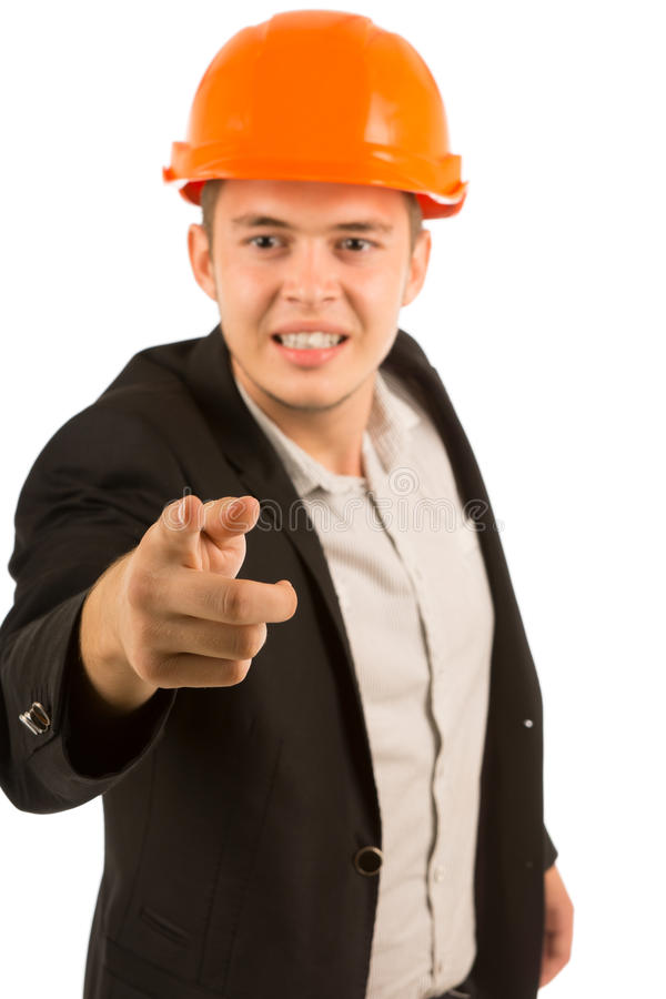Frustrated angry young architect or engineer. In a suit and hardhat gnashing his teeth in anger and pointing at the camera, upper body on white stock photography