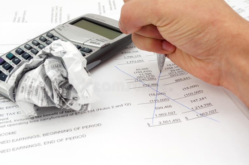 Frustrated Audit man. A photo shows a man's hand with calculater and pen and papers trying to make his own audit but it's not working and he is so frustrated stock photo