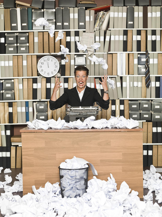 Frustrated Author. Frustrated Female Author in a messy office stock image