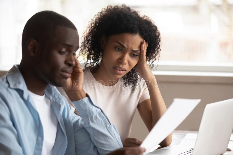 Frustrated biracial couple feel disappointed with financial problems. Troubled pensive biracial young couple feel disappointed consider paperwork paying bills royalty free stock image