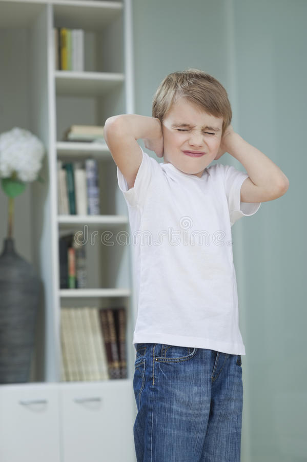 Frustrated boy covering his ears with hands at home stock image