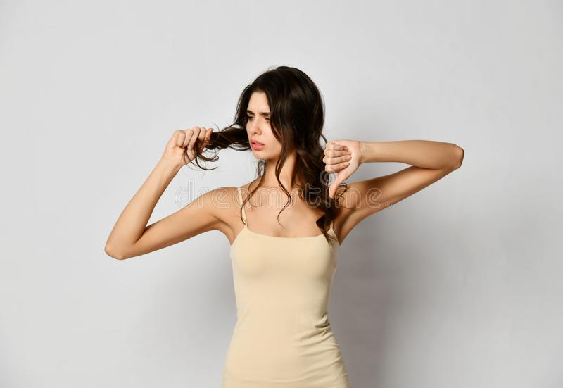 Frustrated brunette woman examining dry damaged hair over gray stock photography