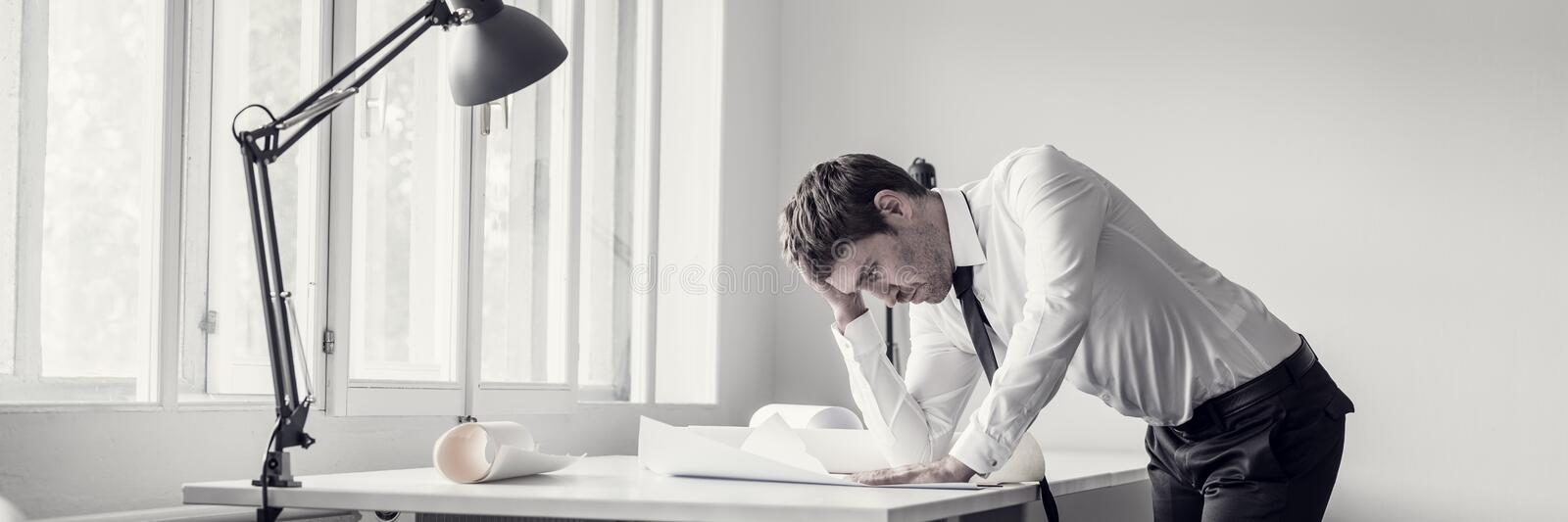 Frustrated business man analyzing plans stock images
