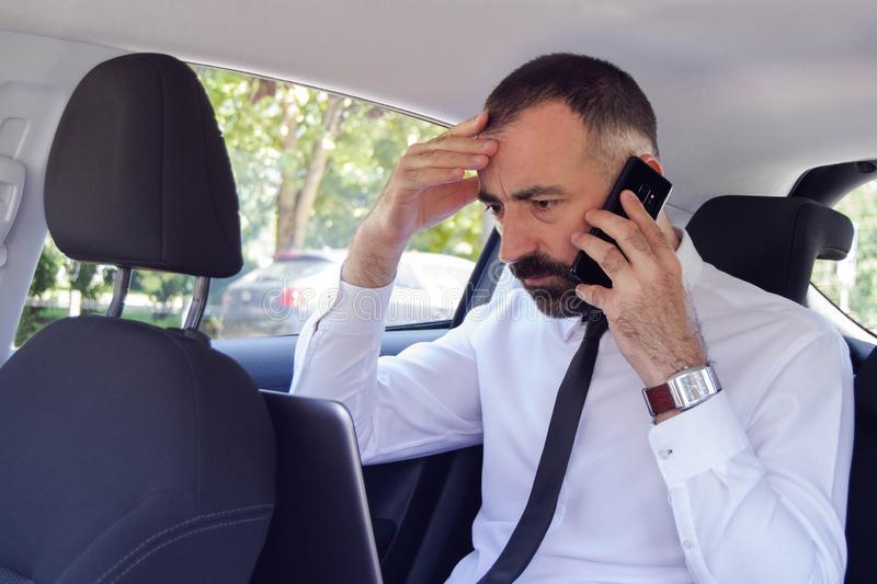Frustrated business man / employee  talking on mobile phone while sitting in the back seat of car. He has a problem and doesn`t know how to solve it royalty free stock photo