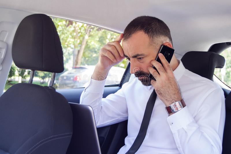 Frustrated business man / employee  talking on mobile phone while sitting in the back seat of car. He has a problem and doesn`t know how to solve it royalty free stock photography