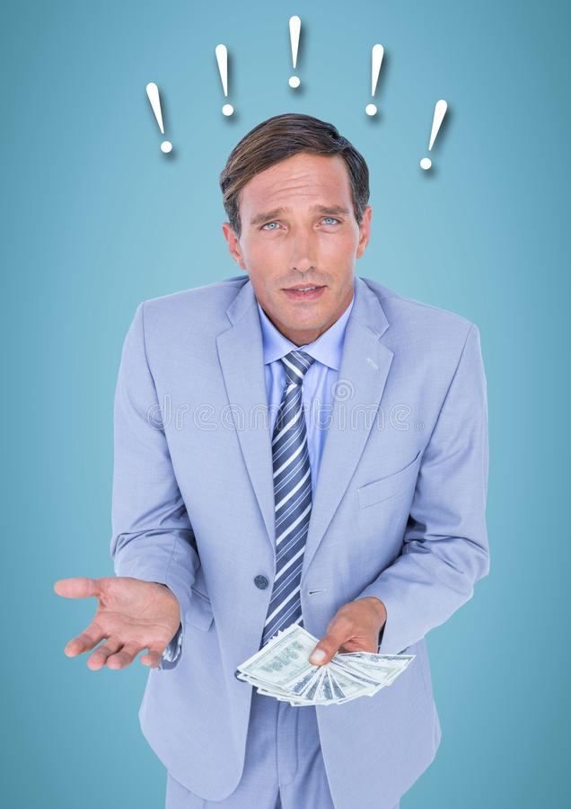 Frustrated business man with money against blue background and exclamation points stock photography