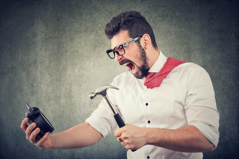 Frustrated business man ready to break an alarm clock with hammer royalty free stock image