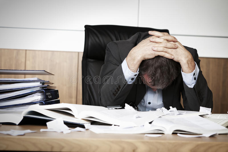 Frustrated business person overloaded with work. Worried businessman in dark suit sitting at office desk full with books and papers being overloaded with work stock images