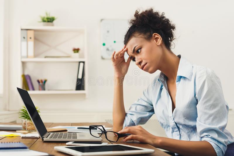 Frustrated business woman with headache at office. Deadline stress concept - sad african-american business woman sitting at desktop in office, working on laptop stock images