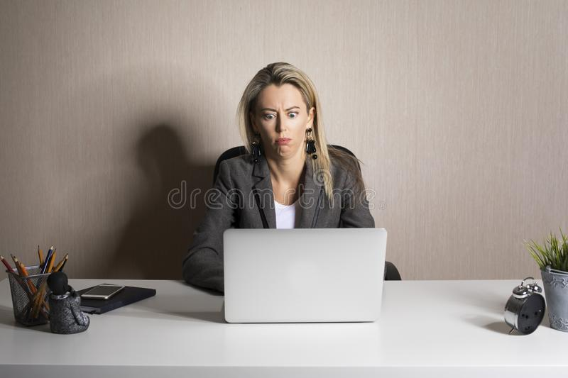 Frustrated business woman  looking at laptop royalty free stock image