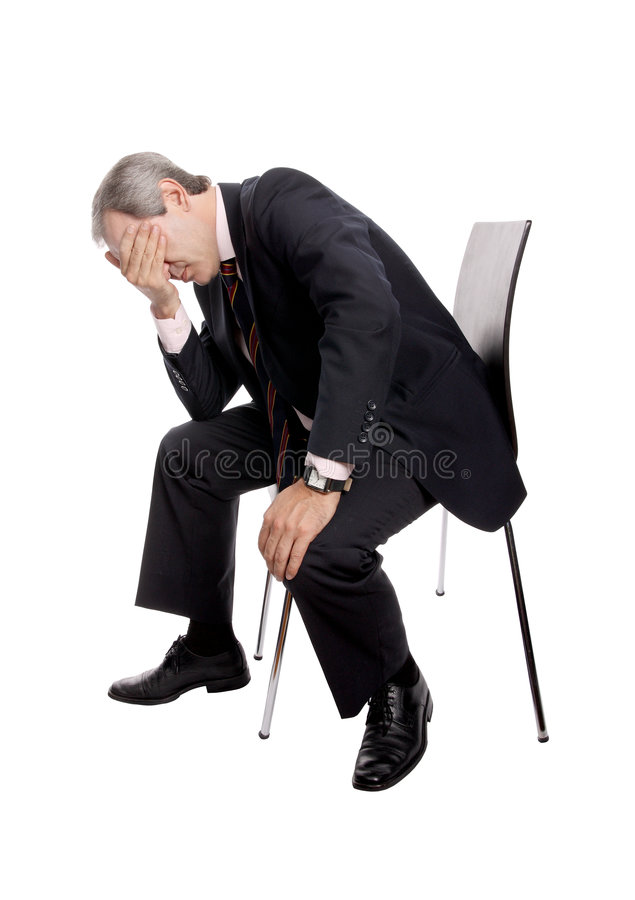 Frustrated businessman. Businessman in despair sitting in a chair isolated on white stock photos