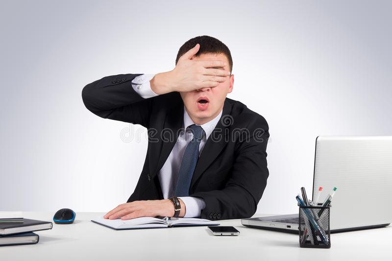 Frustrated businessman close his eyes by hand on gray background royalty free stock photography