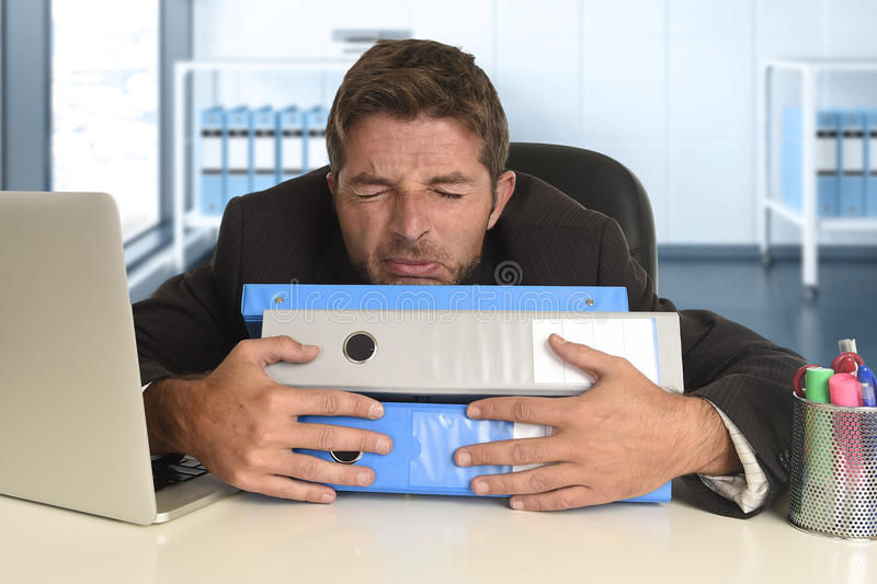 Frustrated businessman desperate face expression suffering stress at office computer desk. Tired and frustrated businessman desperate face expression suffering stock image