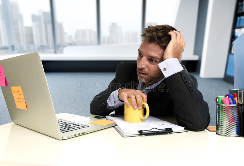 Frustrated businessman desperate face expression suffering stress at office computer desk. Tired and frustrated businessman desperate face expression suffering royalty free stock images