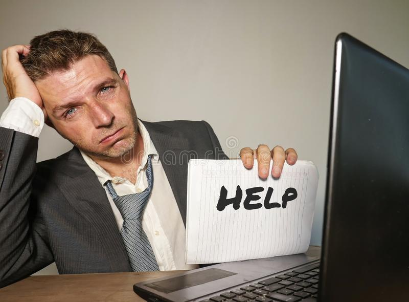 Frustrated businessman desperate at office computer desk holding notepad with the hashtag me too metoo as exploited employee stock images