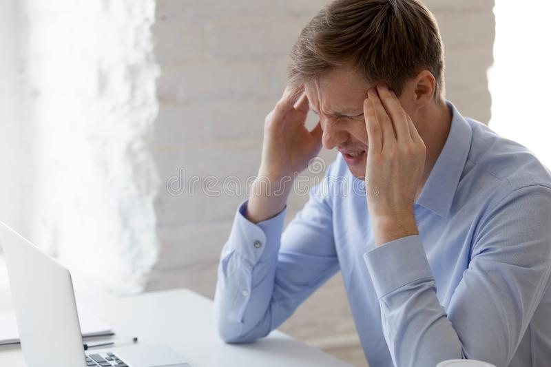 Frustrated businessman feeling pain, massaging temples at workpl. Ace, serious man with closed eyes suffering from headache migraine, tired stressed employee stock photography