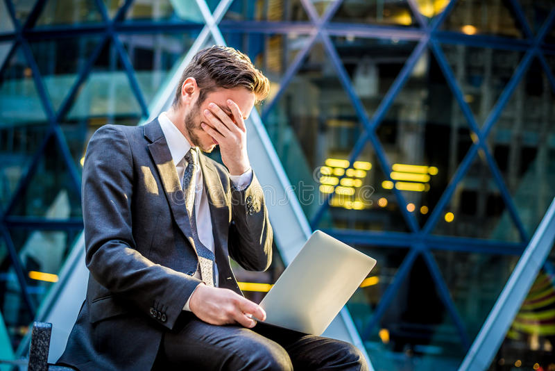Frustrated businessman on laptop computer stock photos