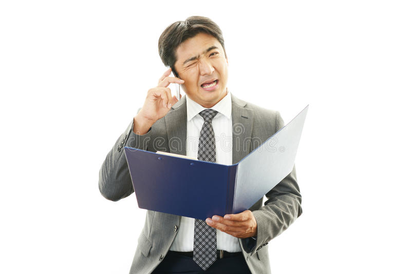 Frustrated Businessman. Stress Asian man with smartphone royalty free stock photo
