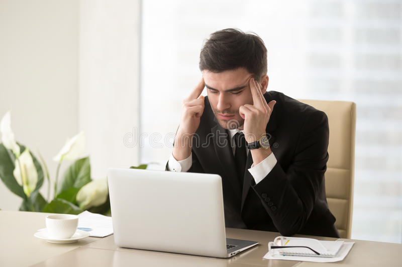 Frustrated businessman suffering from headache migraine at workp royalty free stock photography