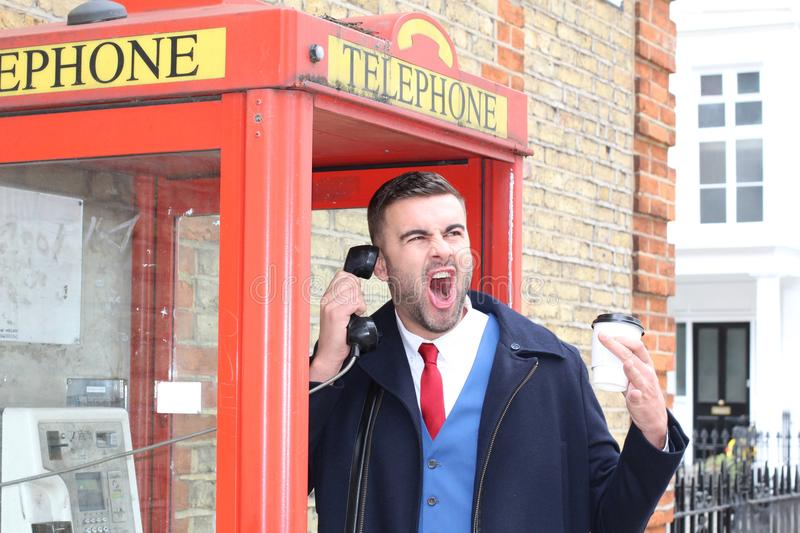 Frustrated businessman in telephone booth stock photography