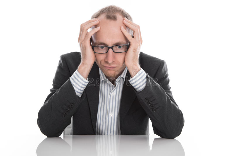 Frustrated businessman wearing glasses sitting at desk with head. In hands isolated on white background stock image
