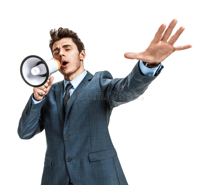 Frustrated businessman yelling through a megaphone. Photos of young businessman wearing a suit and tie over white background royalty free stock images