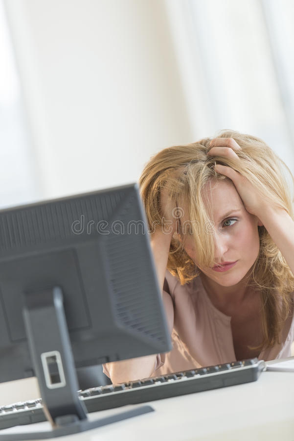 Frustrated Businesswoman Looking At Computer In Office Stock Photo