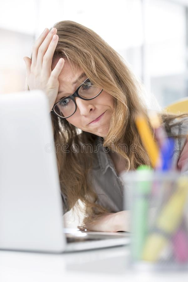 Frustrated businesswoman looking at laptop in office royalty free stock image
