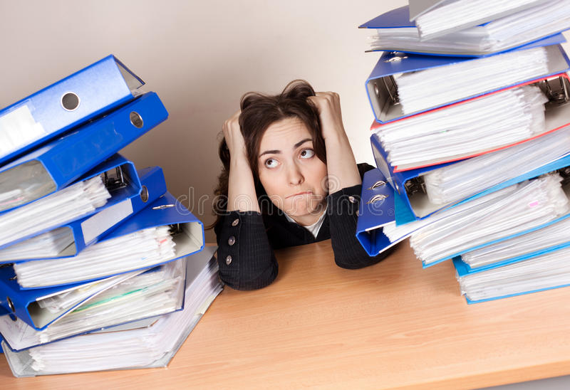 Frustrated businesswoman with stack of folders at office royalty free stock image