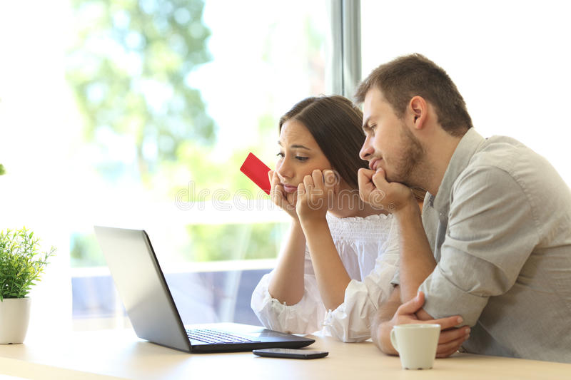 Frustrated buyers trying to pay with card. Frustrated buyers trying to pay online with credit card and a laptop at home stock images