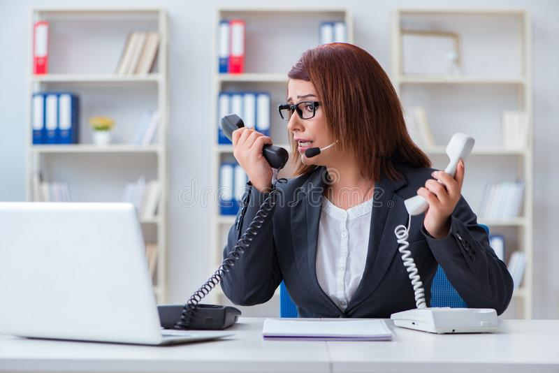 The frustrated call center assistant responding to calls stock photo