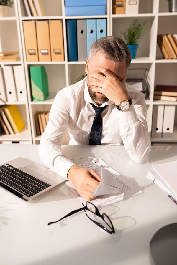 Frustrated cansó al hombre que trabajaba con los papeles en oficina fotos de archivo libres de regalías