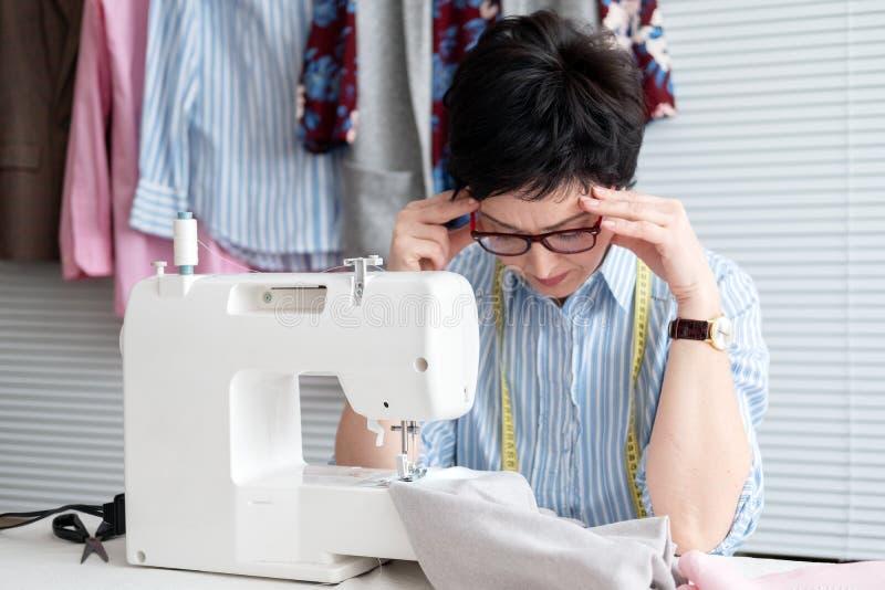 Frustrated cansó a la costurera que tocaba su cabeza, sensación agotada absolutamente debido al trabajo excesivo, trabajando en l imagen de archivo