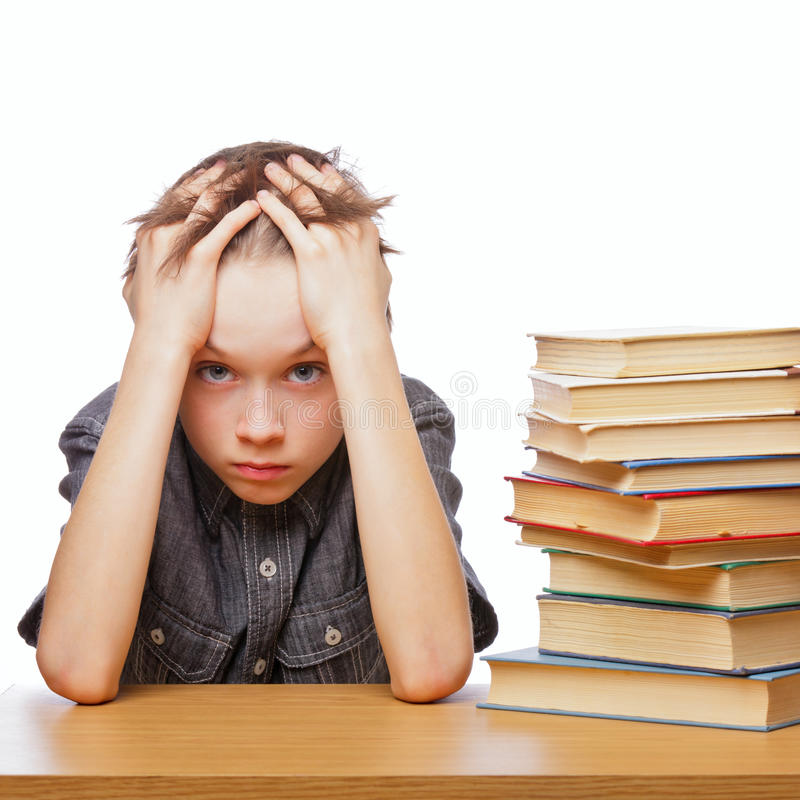 Frustrated child with learning difficulties. Portrait of upset schoolboy sitting at desk with books holding his head royalty free stock photography