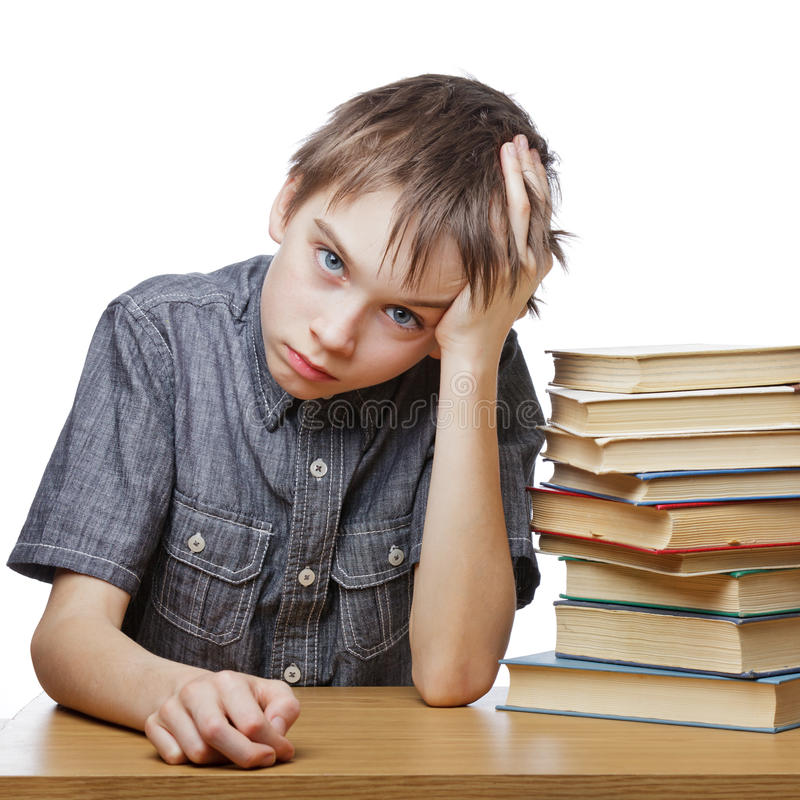 Frustrated child with learning difficulties. Portrait of upset schoolboy sitting at desk with books holding his head royalty free stock photo