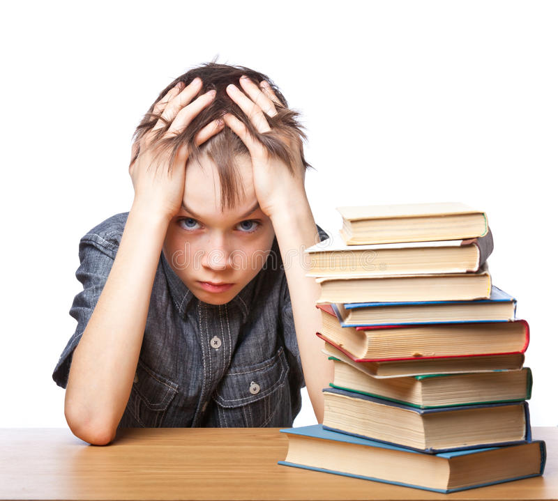 Frustrated child with learning difficulties. Portrait of upset schoolboy sitting at desk with books holding his head royalty free stock images