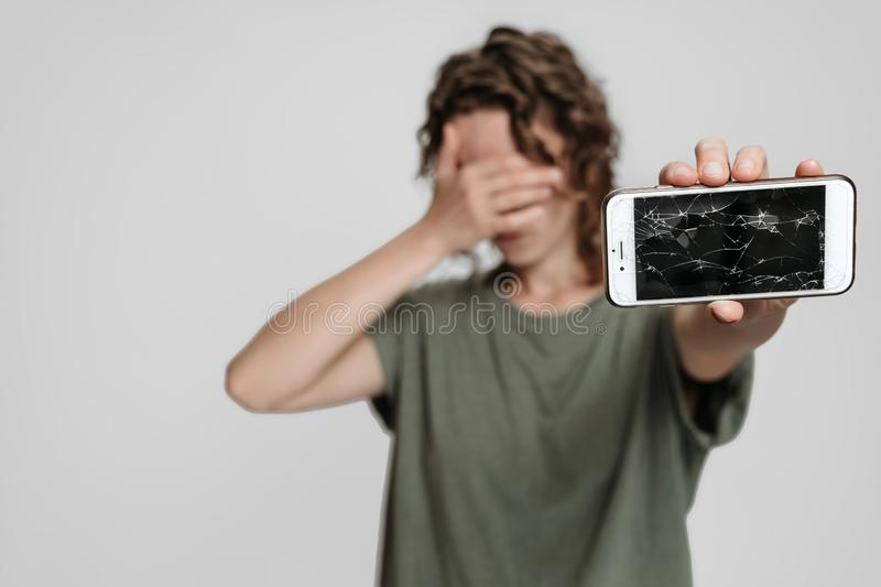 Frustrated curly woman covers face with palm, showing her broken smartphone. Isolated on gray background stock photos