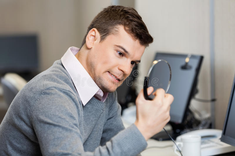 Frustrated Customer Service Representative Holding. Frustrated male customer service representative holding headphones in office stock photos