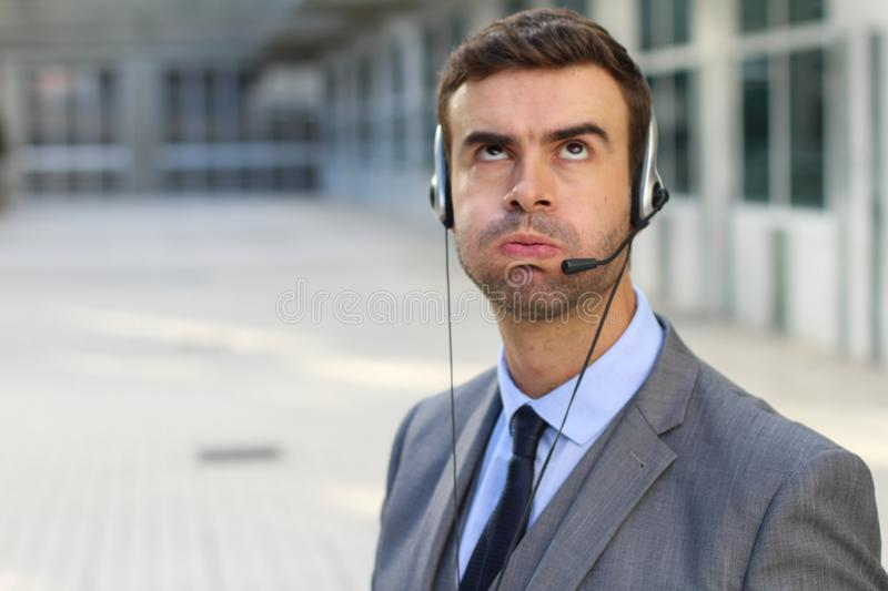 Frustrated customer service worker rolling his eyes.  royalty free stock images