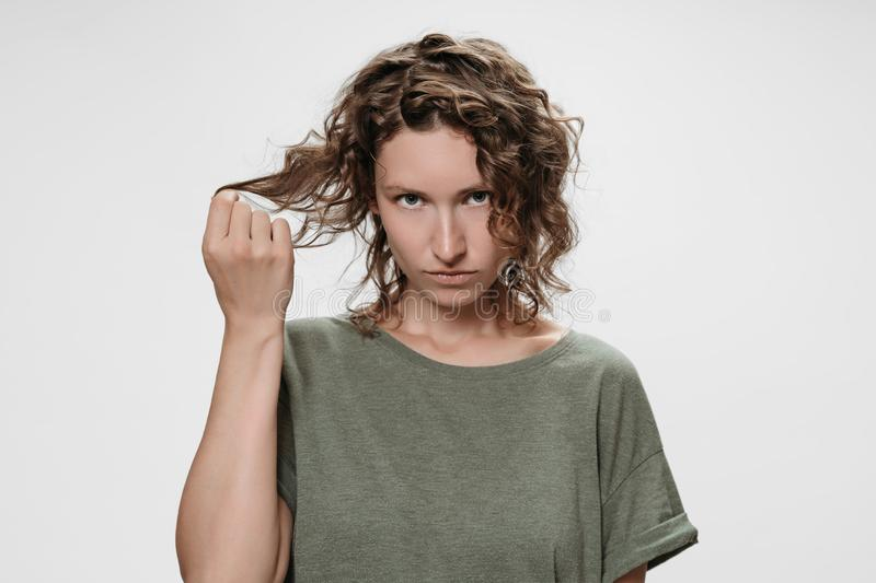 Frustrated discontent young curly brunette woman, frowns face with displeasure. Frustrated discontent curly brunette woman, frowns face with displeasure, holding royalty free stock photos