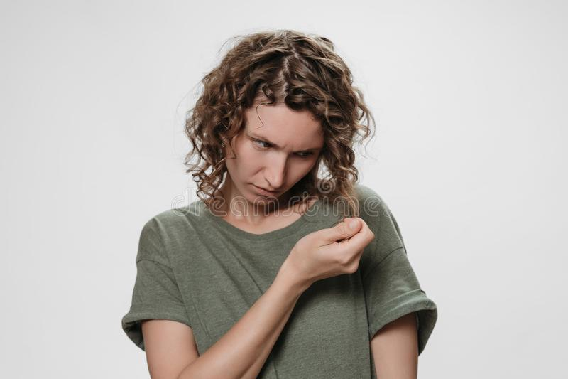 Frustrated discontent young curly brunette woman, frowns face with displeasure. Frustrated curly brunette woman, frowns face with displeasure, holding messed royalty free stock images