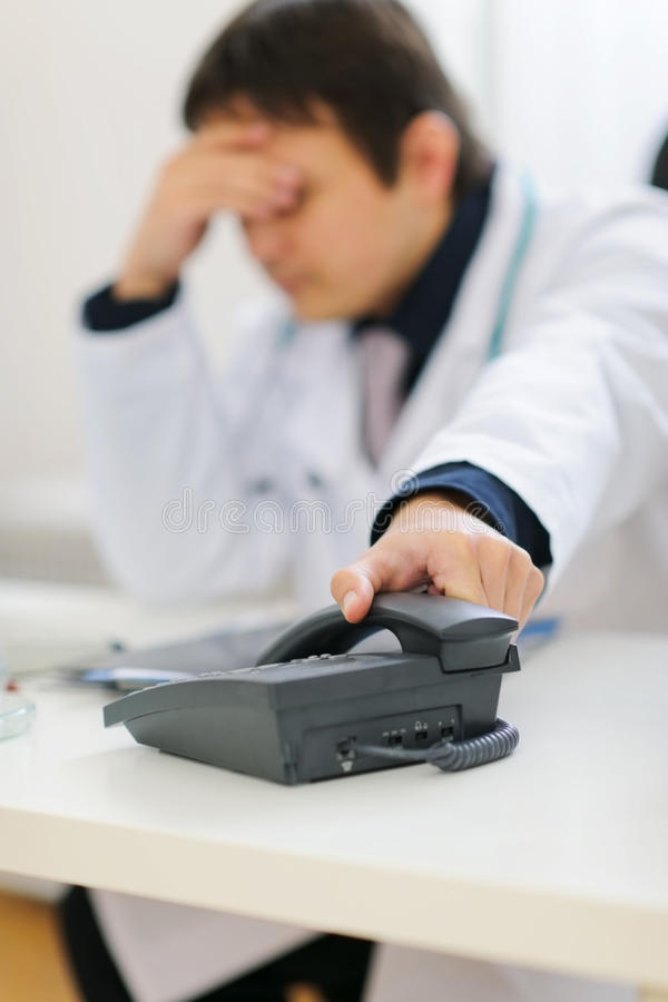Frustrated doctor picking up phone handset. Frustrated medical doctor picking up phone handset stock photos