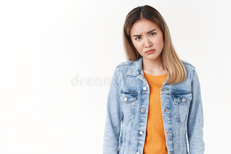 Frustrated doubtful young intense asian blond girl frowning cringe hesitant squinting suspicious have uncertain opinion. Cannot understand disliking hideous royalty free stock photography