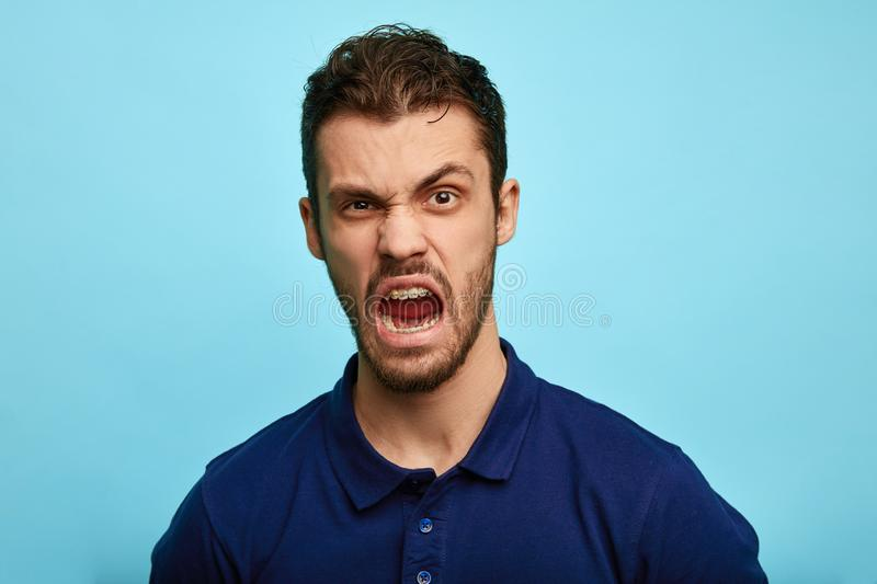 Frustrated, enraged man with grumpy grimace on his face,. Scolding somebody, expresses negative emotion, irritation concept royalty free stock photo