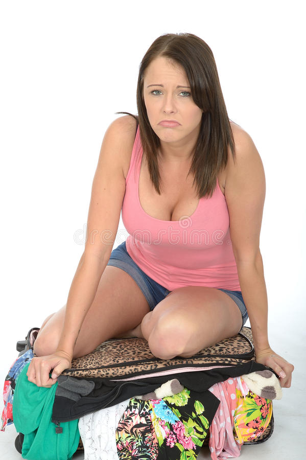 Frustrated Fed Up Unhappy Young Woman Trying to Close an Overflowing Suitcase by Sitting on It stock photography