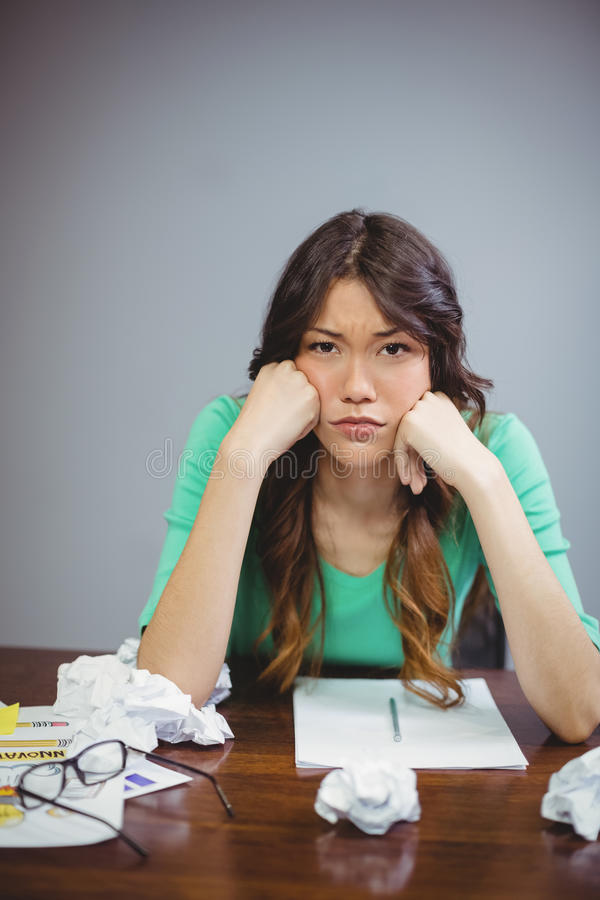 Frustrated female executive sitting with crumpled papers balls royalty free stock photo