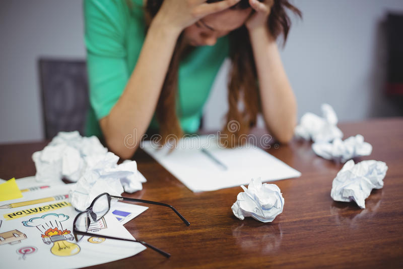 Frustrated female executive sitting with crumpled papers balls stock photography