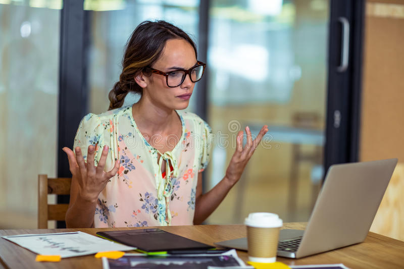Frustrated female graphic designer looking at laptop stock photos